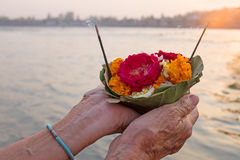 Doing puja at the river Ganges in India at sunset Stock Photos