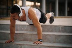 Doing push up exercise. Male runner doing push up exercise , preparing for morning workout outdoors. While doing a stretching exercise, he listens to music via Stock Photo