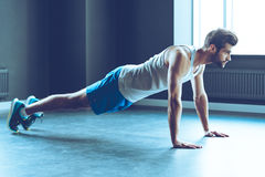 Doing push-up. Full length of young handsome man in sportswear doing push-up at gym Stock Photos