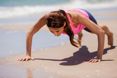 Doing push-ups at the beach stock photography