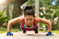 Doing push-ups. Sporty Asian woman doing push-ups outdoors Royalty Free Stock Images