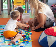 Doing puzzle with tutor in nursery Royalty Free Stock Photography