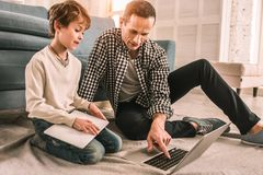 Experienced knowledgeable adult showing his son news from the Internet. Doing research. Young boy looking up necessary information online stock photo