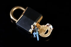 Doing A Security Check. Overhead view on black of two miniature figures of workmen turning a key in a padlock to check up on security Stock Images