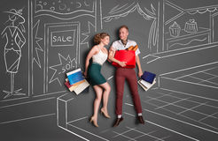 Doing shopping. Love story concept of a romantic couple on shopping against chalk drawings background. Young happy couple standing together with shopping bags stock illustration