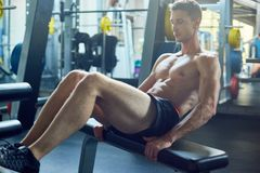 Doing Sit ups at Gym. Handsome young athlete with muscular bare torso doing sit ups while having workout at spacious gym, full length portrait stock image
