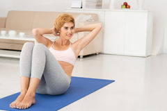 Doing sit-ups. Smiling pretty woman doing sit-ups at home Stock Photo