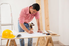 Doing some design work. Young Latin man drawing and modifying a house design Royalty Free Stock Photos