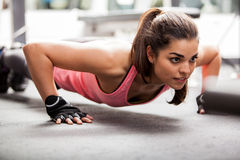 Doing some push ups at the gym. Beautiful Latin woman doing push ups in the gym before lifting some weights Royalty Free Stock Photos
