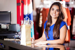 Doing some shopping at a mall. Happy young woman doing some shopping in a clothing store and smiling stock photos