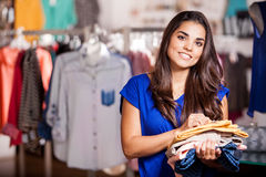 Doing some shopping at the mall. Wider shot of a beautiful young woman shopping some clothes in a clothing store and smiling stock photography