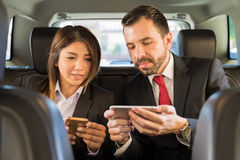 Doing some work on the way to the office. Good looking couple of businesspeople using the ride to the office to do some work on their smartphones Stock Image