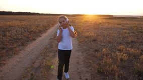 Doing sports jogging at sunset outside city. young girl in a white T-shirt trains at sunset and listens to music with. Doing sports jogging at sunset outside stock video footage
