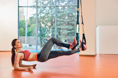 Doing sporty girl plank with strap. Fit girls in gym doing plank exercise for back spine with trx strap stock photo