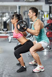 Doing squats with barbell helped by personal instructor Stock Image