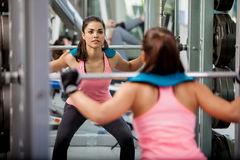 Doing squats with a barbell. Pretty Latin brunette doing some squats with a barbell and focusing on her routine Royalty Free Stock Photography