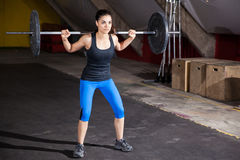 Doing squats at a gym. Beautiful Hispanic woman doing some squats with a barbell in a cross-training gym Stock Photography