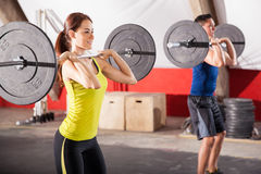 Doing squats at a gym. Cute brunette and a guy doing some squats with barbells in a gym Royalty Free Stock Photography