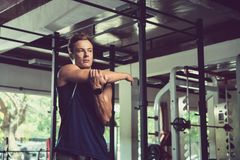Doing Stretching Exercise for Arms. Waist-up portrait of sporty handsome man looking away while doing stretching exercise for arms, interior of spacious gym on Royalty Free Stock Photo