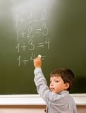 Doing sums. Portrait of pensive schoolchild standing at blackboard and doing sums Royalty Free Stock Image