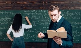 Doing sums. Rear view woman write equation on chalkboard. Learning math enables me to think clearly. Teacher man in. Doing sums. Rear view women write equation royalty free stock photos