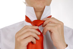 Doing a tie. Business men is fixing his red tie. You can see just his hands and part of the tie royalty free stock photo