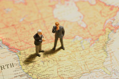 Doing the world. Business people on mapworld discussing about future or businesses Stock Photo