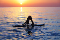 Doing yoga on the beach. Sportive female doing yoga exercise on the beach over beautiful sunset background, standing on the sup board on the water in Pose dog Stock Photo