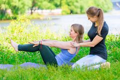 Doing yoga exercise with an individual experienced trainer. In the park stock image