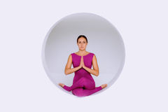 Doing yoga exercises in creative studio. Sporty woman in active wear, practicing  yoga exercises in geometric  design of round shapes,in sphere Royalty Free Stock Photo