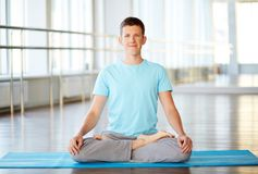 Doing yoga. Portrait of young man doing yoga exercise in gym Royalty Free Stock Image