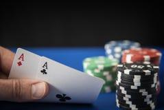 Dois áss à disposição e microplaquetas de jogo no feltro do azul do casino Imagens de Stock