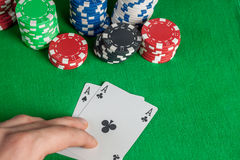 Dois áss e pilhas das microplaquetas de pôquer na tabela verde Foto de Stock