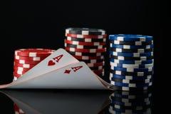 Dois áss vermelhos em cartões do pôquer na perspectiva das estacas do pôquer Fotos de Stock