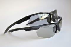 Dois óculos de sol do preto do esporte com efeito photochromic e polarizando, um no outro, no fundo branco imagem de stock