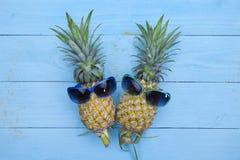 Dois abacaxis em óculos de sol à moda no backgrou de madeira azul fotografia de stock royalty free