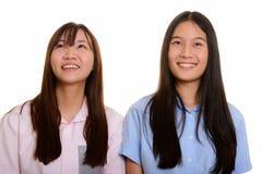 Dois adolescentes asiáticos felizes novos que sorriem e que pensam imagem de stock royalty free