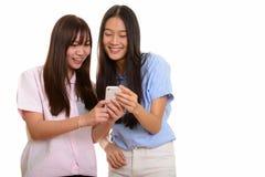 Dois adolescentes asiáticos felizes novos que sorriem e que usam o pho móvel fotografia de stock