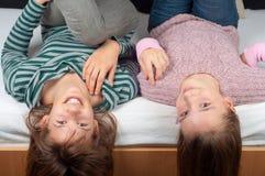 Dois adolescentes bonitos que encontram-se na cama Fotos de Stock