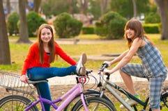 Dois adolescentes bonitos que têm o divertimento em bicicletas Fotografia de Stock Royalty Free