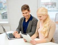 Dois adolescentes com o PC do portátil e da tabuleta na escola Fotografia de Stock