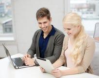 Dois adolescentes com o PC do portátil e da tabuleta na escola Fotografia de Stock Royalty Free