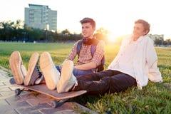Dois adolescentes em um bom humor com um skate Fotografia de Stock Royalty Free