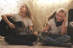 Dois adolescentes fêmeas que jogam instrumentos musicais, guitarra e flauta, em casa fotografia de stock