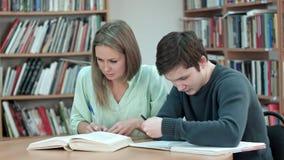 Dois adolescentes que estudam na biblioteca Fotos de Stock Royalty Free