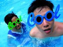 Dois adolescentes que vestem óculos de sol com a palavra esfriam para seu quadro em uma piscina Fotografia de Stock Royalty Free