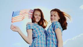 Dois adolescentes redheaded com uma bandeira americana Sorriso, olhar na câmera vídeo de movimento 4K lento video estoque