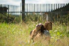 Dois adolescentes são amigos que sentam-se em um esclarecimento sob o sol verão Fotografia de Stock