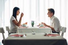 Dois adultos novos ocasionais que têm uma conversação sobre uma refeição Proposta formal, falando em um restaurante Alimento de t foto de stock