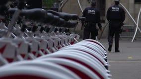 Dois agentes da polícia masculinos no dever, patrulhando o centro da cidade, indo postar filme